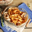 Tasty french fries and fresh potatoes in metal baskets on wooden table background — Stock Photo #68118285