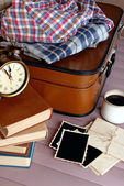 Vintage suitcase with clothes and books om wooden background — Zdjęcie stockowe