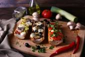 Different sandwiches with vegetables and cheese on cutting board on table close up — Foto de Stock