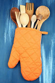 Different kitchen utensils in potholder on wooden background — Stock Photo