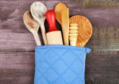 Different kitchen utensils in potholder on wooden background — Stock Photo