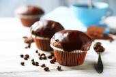 Tasty homemade chocolate muffins and cup of coffee on wooden table — Stock Photo