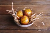 Easter eggs in bowl on wooden background — Stock Photo