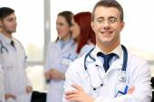 Attractive male doctor with team in conference room — Stockfoto