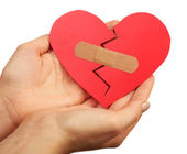 Female hands holding broken heart with plaster isolated on white — Stock Photo