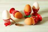 Boiled eggs in holders on light   background — Stock Photo