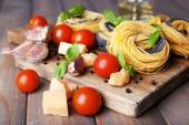 Raw pasta with cheese and vegetables on wooden background — Stock Photo