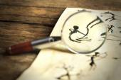 Rock paintings with magnifier on paper on wooden table close up — Stock Photo