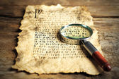 Grunge paper with hieroglyphics with magnifier on wooden background — Stock Photo