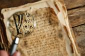 Grunge papers with hieroglyphics with magnifier close up — Stock Photo