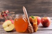 Delicious honey with apple on table on wooden background — Stock Photo