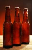 Glass bottles of beer on wooden table on dark background — Foto de Stock