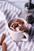 Cup of cocoa with marshmallows on tray and stripped napkin, closeup — Stock Photo