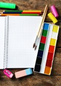 Notebook and bright school stationery on old wooden table — Stock Photo