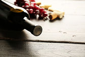 Glass bottle of wine with corks and grapes on wooden table background — Stockfoto