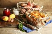 Tasty french fries and fresh potatoes in metal baskets on wooden table background — Stock Photo