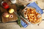 Tasty french fries in metal basket on wooden table background — Stock Photo