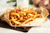 Tasty french fries on paper napkin, on wooden table background — Stock Photo