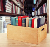 Books in wooden crate on bookshelves background — Foto de Stock