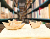 Open book with paper ships on bookshelves background — Stockfoto