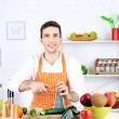 Man at table with different products and utensil in kitchen on white wall background — Stock Photo #68292755