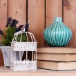 Interior design with decorative vase, cage, plant and stack of books on tabletop on wooden planks background — Stock Photo #68294305
