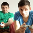 Two handsome young men playing video games in room — Stock Photo #68297665