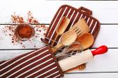 Set of kitchen utensils with cocoa in mitten on wooden background — Stock Photo