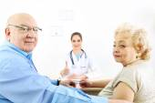 Happy doctor and patients in hospital clinic — Stock Photo