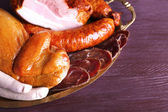 Assortment of deli meats on metal tray on color wooden background — Stock Photo
