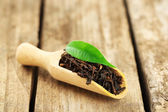 Black tea with leaf in scoop on old wooden table — Stock Photo