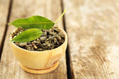Green tea with leaf in bowl on old wooden table — Stock Photo
