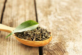 Green tea with leaf in spoon on old wooden table — Stock Photo