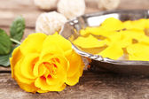 Rose flower and petals in bowl on wooden background — Stock Photo