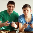 Two handsome young men playing video games in room — Stock Photo #68526709