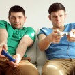 Two handsome young men playing video games in room — Stock Photo #68526711
