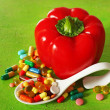 Paprika and colorful pills, on wooden background — Stock Photo #68527177