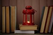 Books and decorative lantern on table and wooden planks background — Stock Photo
