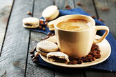 Gentle colorful macaroons and  coffee in mug on wooden table background — Stock Photo