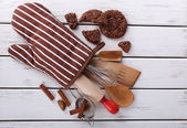 Set of kitchen utensils with cookies in mitten on wooden background — Stock Photo