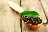 Black tea with leaf in spoon on old wooden table — Stockfoto