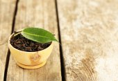 Black tea with leaf in bowl on old wooden table — Fotografia Stock