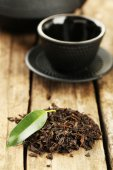 Black tea with leaf on old wooden table — Stockfoto