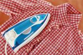 Iron and shirt on board close up — Stock Photo