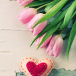 Beautiful pink tulips with decorative heart on wooden background — Stock Photo #68607923