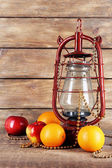 Kerosene lamp with beads and fruits on wooden planks background — Stock Photo