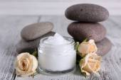 Cosmetic cream with flowers and spa stones on wooden background — Photo