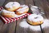Delicious donuts with icing and powdered sugar on wooden background — Stock Photo