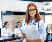 Beautiful young doctor with team in conference room — Stock Photo