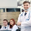 Attractive male doctor with team in conference room — Stock Photo #68610021